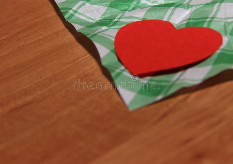 Na drewnianej powierzchni na dekoracyjnym papierze w zieleni klatka kłama czerwonego serce fotografia stock