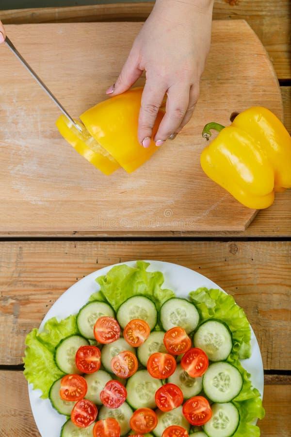 Na drewnianej tnącej deski kobiecie kraść żółtego pieprzowego nóż obrazy royalty free