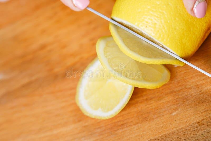 Na drewnianej tnącej deski kobiecie kraść żółtego pieprzowego nóż zdjęcie stock