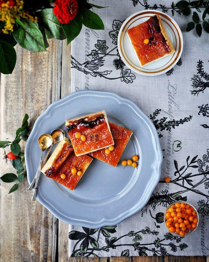 Na drewnianym stole na błękitnym talerzu jest curd tort z buckthorn Dekorujący z kwiatami i gałąź z biodrami obraz royalty free