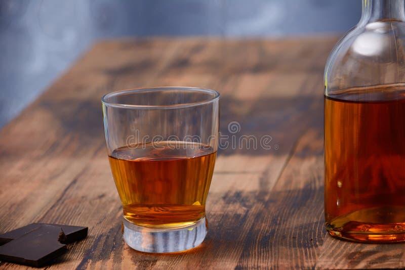 Na drewnianym stole jest szkło koniak, przekąska kawałek ciemna czekolada i butelka alkohol, obrazy stock