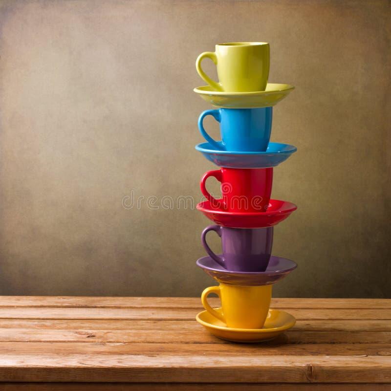 Na drewnianym stole kolorowe filiżanki zdjęcie royalty free