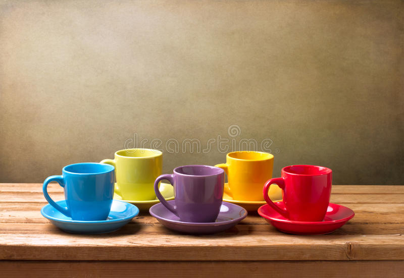 Na drewnianym stole kolorowe filiżanki obrazy stock