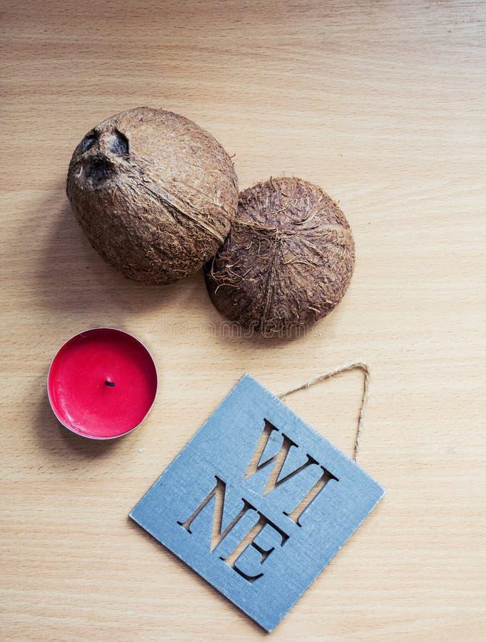 Na drewnianym stole oddzielnie warty czerwoną świeczkę ` wina ` pastylka z inskrypcją Kokosowa skorupa na beżowym drewnianym stol fotografia stock