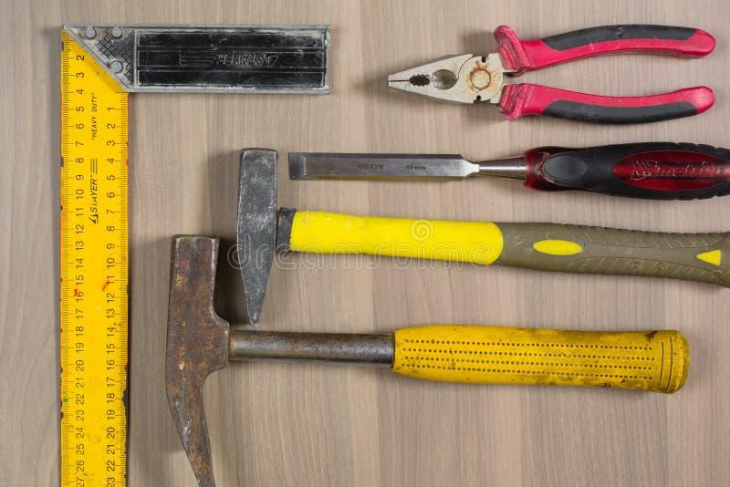 Na drewnianym tle różni narzędzia Młot, ścinak, cążki, kwadrat zdjęcia stock