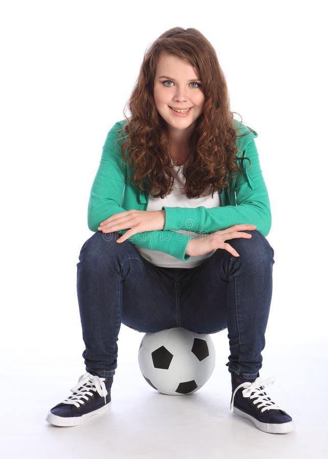 Na esfera um jogador de futebol alegre da menina do adolescente fotografia de stock royalty free