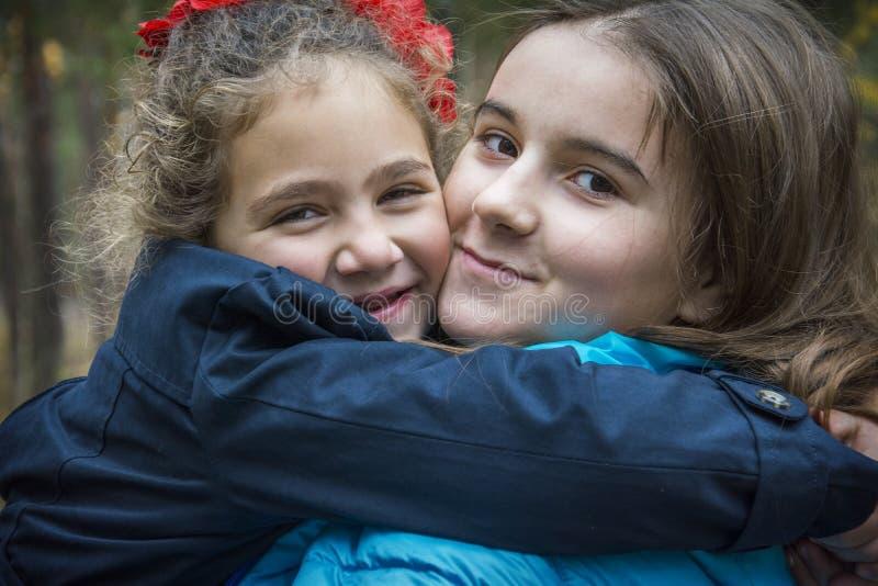 Na floresta do outono, dois amigos felizes abraçam fotografia de stock royalty free
