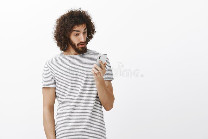 Na het oude ex-meisje roepen Verraste overweldigde gevoelskerel met krullende haar en baard, die bij smartphone staren royalty-vrije stock afbeelding