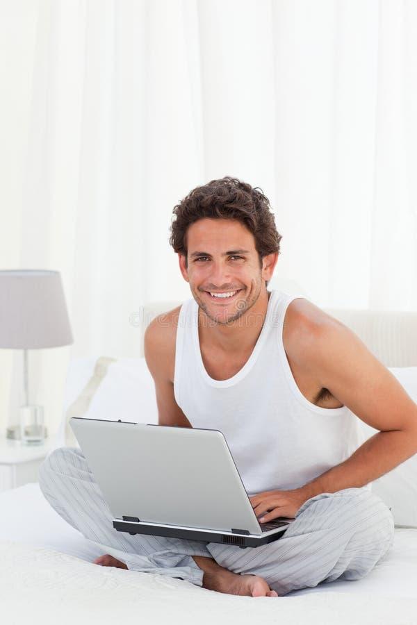 Na jego laptopie mężczyzna działanie w domu zdjęcia royalty free