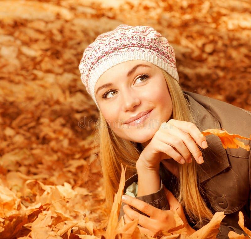 Na jesiennych liść ładna kobieta zdjęcie royalty free