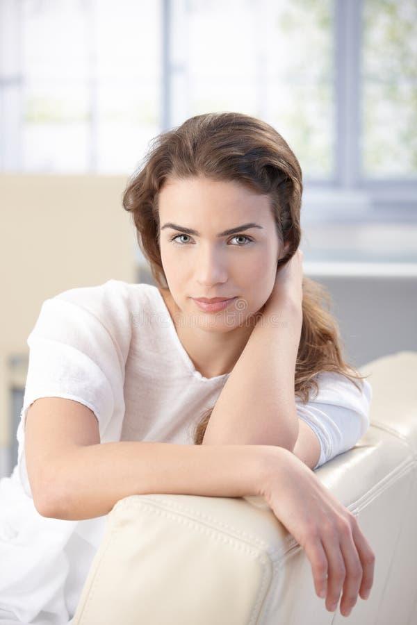 Na kanapie kobiety piękny obsiadanie w domu zdjęcia stock
