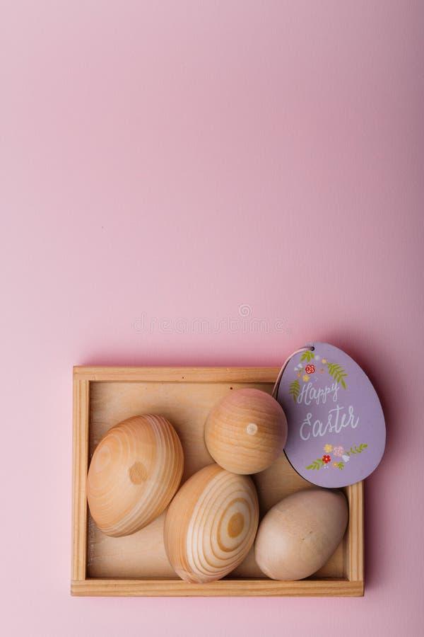 Na koralowym tle w drewnianym pudełku są drewniani puste miejsca jajka purpurowa owalna karta z wpisową Szczęśliwą wielkanocą obrazy royalty free
