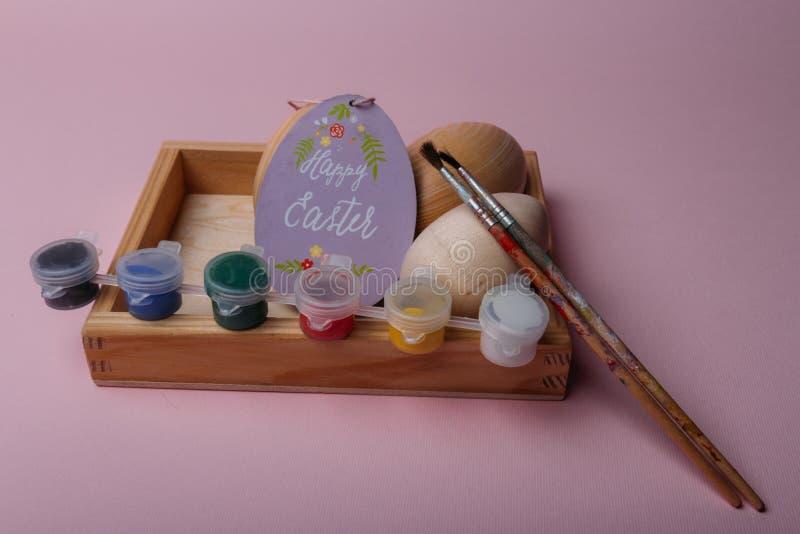 Na koralowym tle w drewnianym pudełku są drewniani puste miejsca jajka purpurowa owalna karta z wpisową Szczęśliwą wielkanocą bli zdjęcia stock