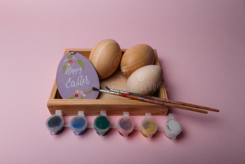 Na koralowym tle w drewnianym pudełku są drewniani puste miejsca jajka purpurowa owalna karta z wpisową Szczęśliwą wielkanocą bli obrazy royalty free