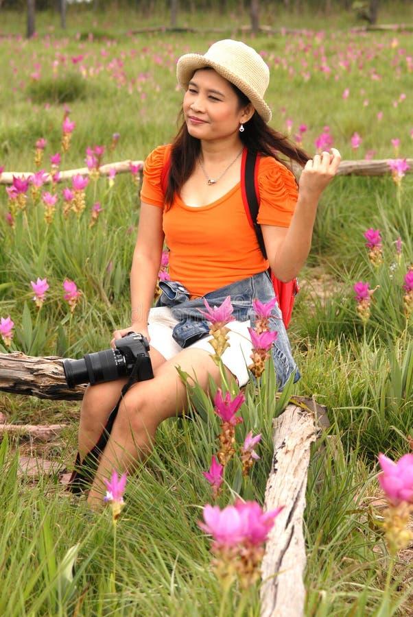 Na kwiatu polu kobiety ładny Azjatycki obsiadanie. zdjęcia royalty free