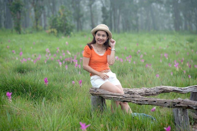 Na kwiatu polu kobiety ładny Azjatycki obsiadanie. zdjęcia stock