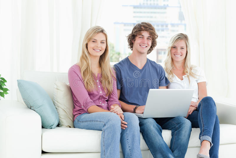Na leżance uśmiechnięci ludzie gdy one używać laptop zdjęcia royalty free