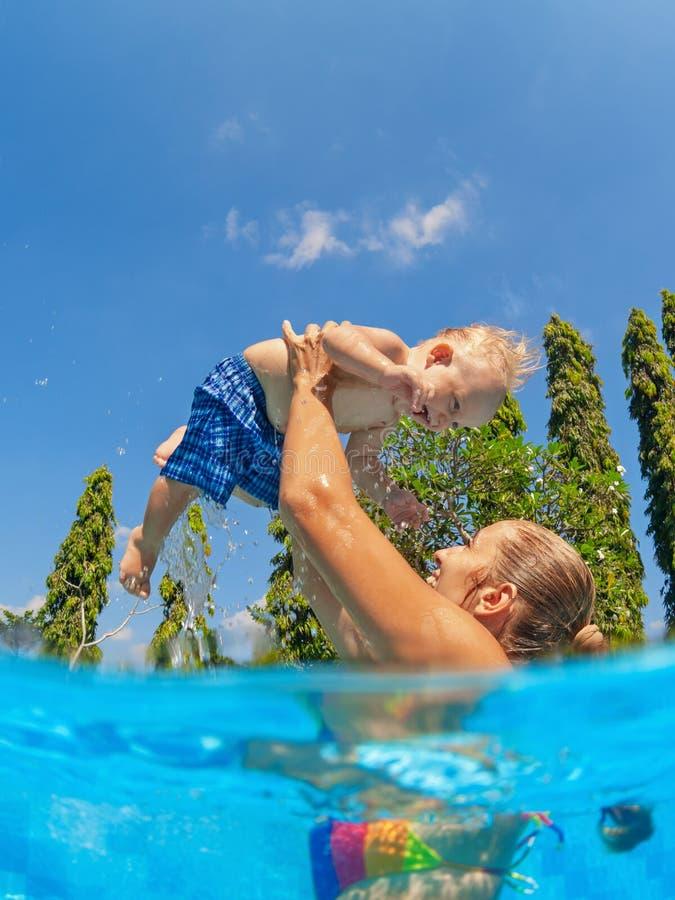 Na m?e da piscina que lan? no filho pequeno do beb? do ar fotografia de stock