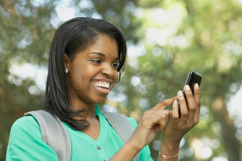 Na mądrze telefonie Amerykanin afrykańskiego pochodzenia młoda kobieta obraz stock