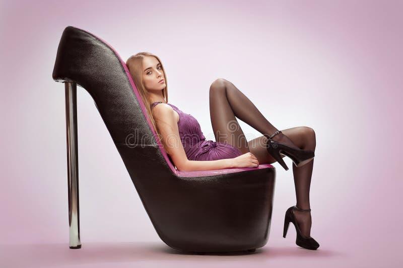 Na młodej kobiety obsiadanie modni buty zdjęcia royalty free