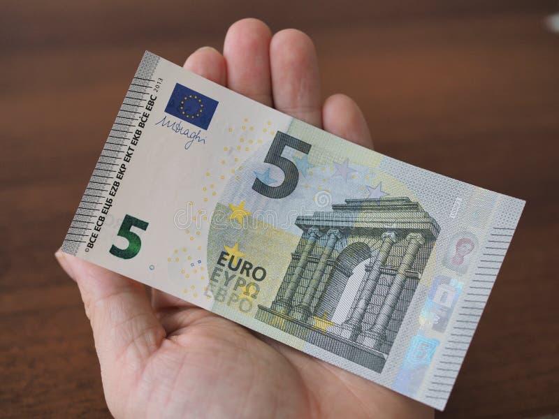 Na m?o humana encontra-se um Euro novo bonito da conta 5 close-up, borr?o foto de stock royalty free
