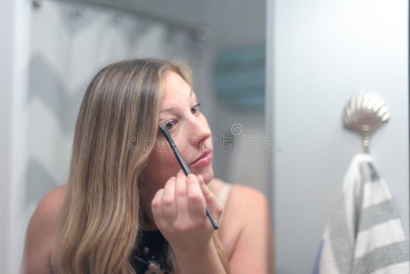 Na makeup młodej kobiety kładzenie obrazy stock