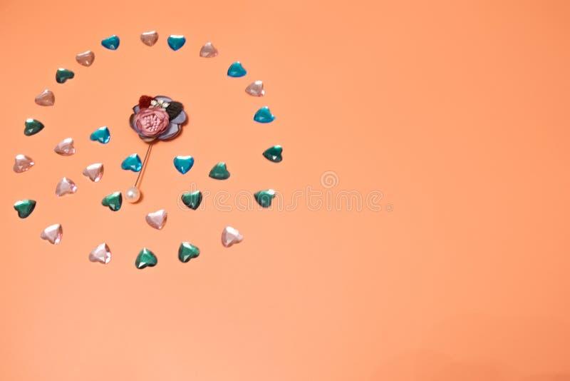 Na menchii, beżowy tło tam jest wiele różnymi małymi sercami robić klingeryt jak rhinestones obrazy stock