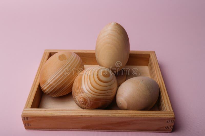 Na menchii tło jest drewnianym stojakiem w którym są drewniani jajka, puste miejsca, Wielkanocni jajka obrazy stock