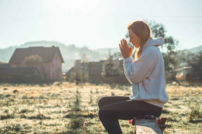 Na menina da manhã fechado seus olhos, rezando fora, as mãos dobraram-se no conceito da oração para a fé, espiritualidade, concei imagens de stock