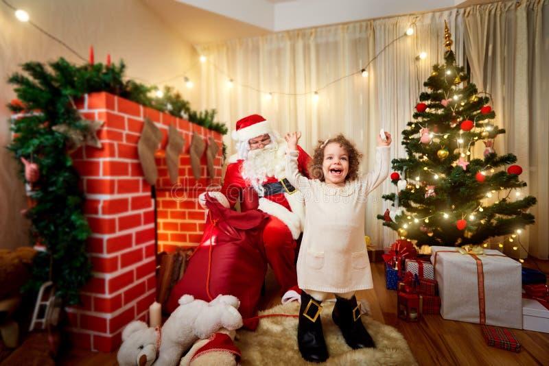 Na menina encaracolado do Natal nas botas com Santa Claus no imagem de stock royalty free