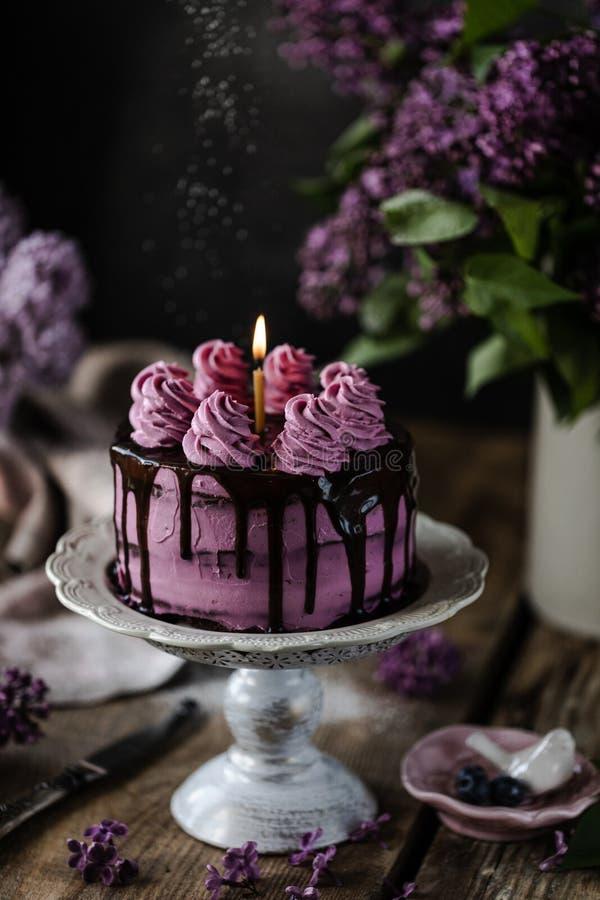 Na mesa está um belo bolo de chocolate e um buquê de lilases escuro fotografia de stock