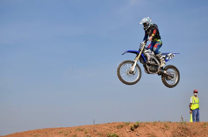 Na motocicleta um cavaleiro salta sobre um monte alto da terra foto de stock