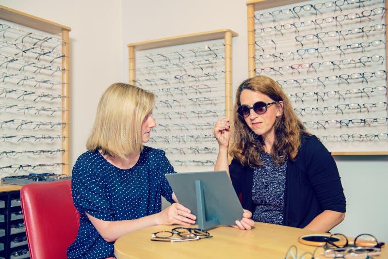 Na mulher da loja do ótico que seleciona óculos de sol novos fotografia de stock royalty free