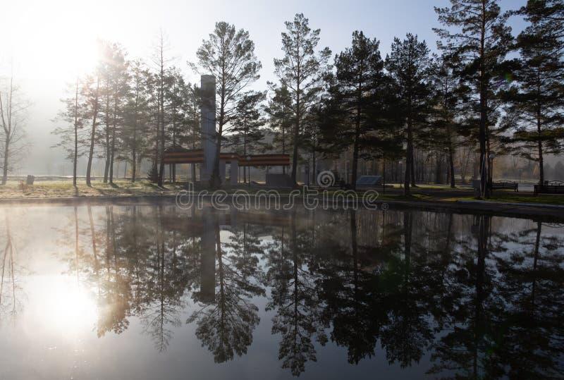 Na névoa da manhã, o vapor aumenta da lagoa da água, p foto de stock