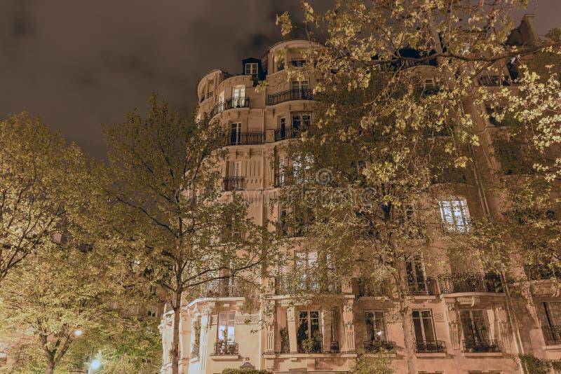 Na noite uma casa bonita alta cercada por árvores altas é iluminada por lanternas fotografia de stock