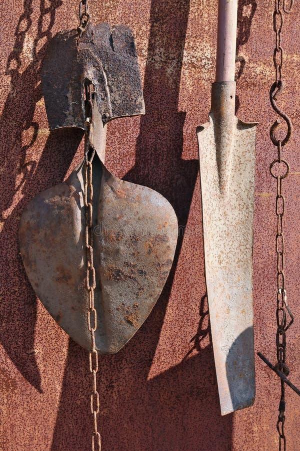 Na ośniedziałym metalu ściana wioski jaty zrozumienie na łańcuchach używał starego rocznika rolnicze łopaty zdjęcie royalty free