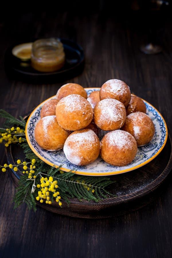Na półkowi donuts z cukieru proszkiem, dekorującym z mimozami kwitną Drewniany tło obrazy stock