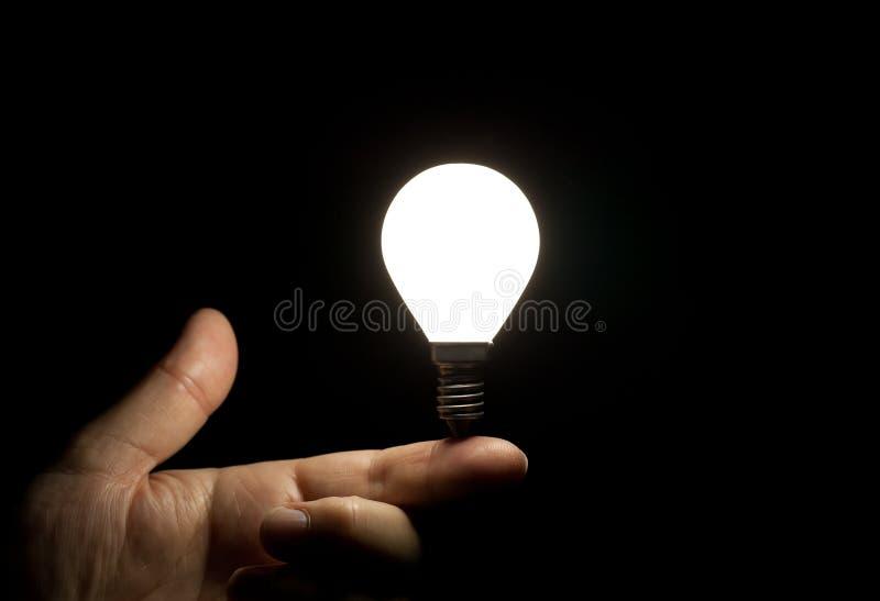 Na palcu żarówki zaświecający równoważenie fotografia stock