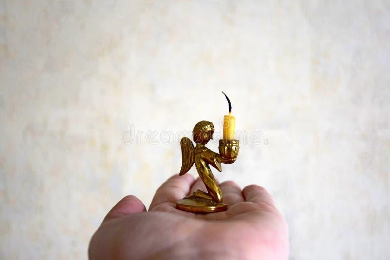 Na palma da mão de uma mulher a vela extinta da igreja imagens de stock