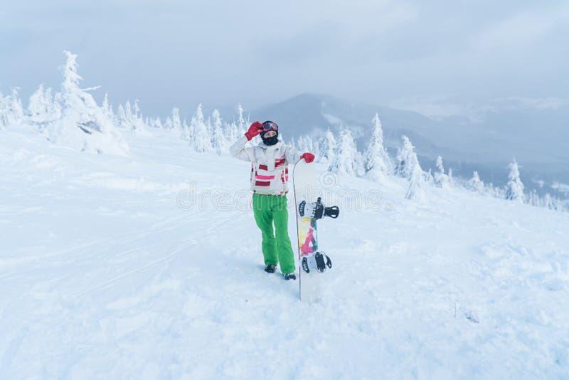 Na parte superior do snowboard da montanha do inverno da montanha Mulher que guardara o Snowboard fotos de stock