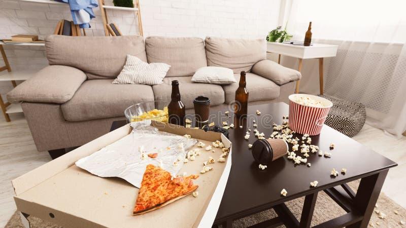 Na partij binnenlandse chaos Bierflessen, popcorn en pizza stock foto