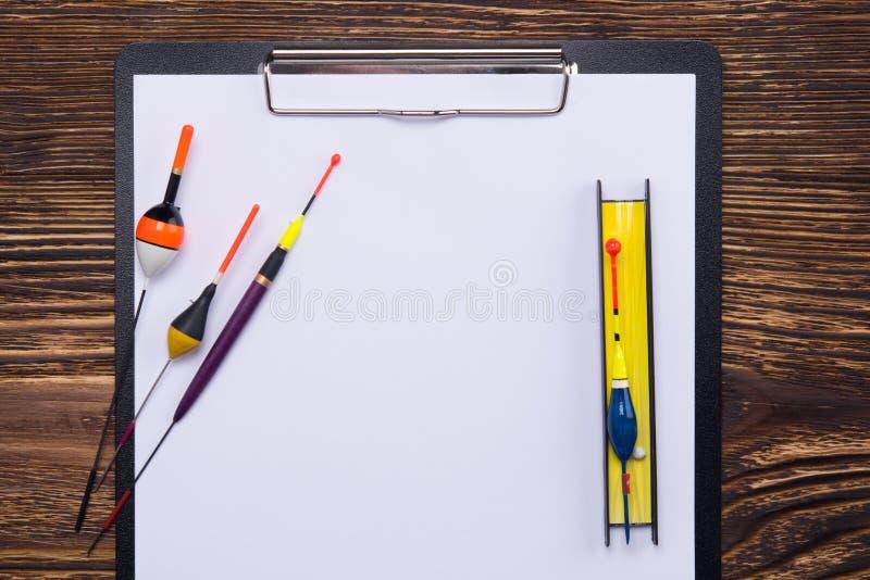 Na perspectiva de uma tabela de madeira escura, de uma tabuleta com espaço para inscrição e linha artigos da pesca, flutuadores e foto de stock