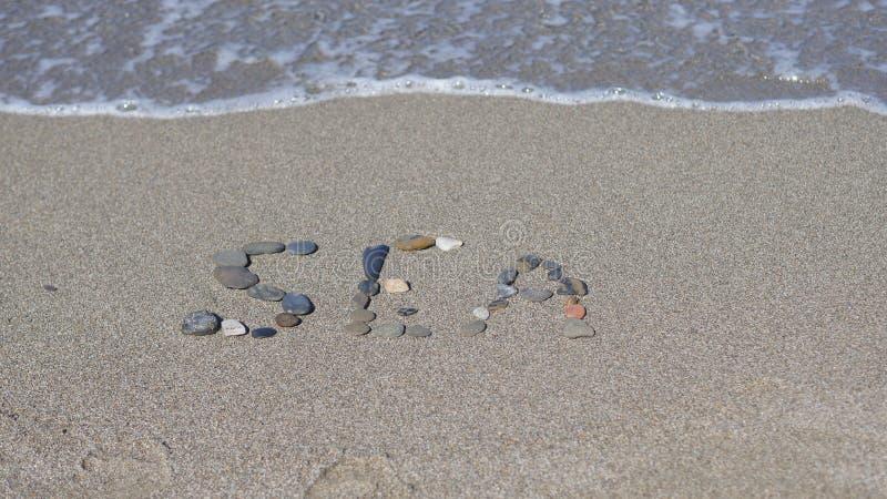 Na piasku inskrypcja Słowo morze obrazy royalty free
