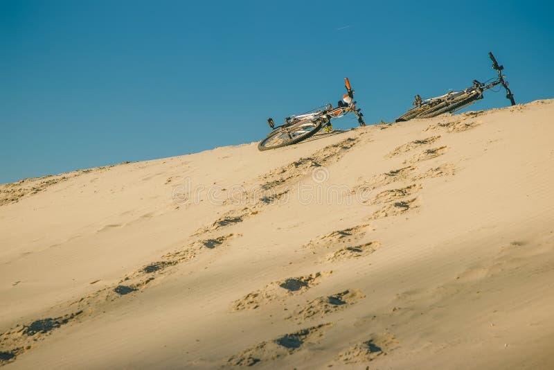 Na plaży pod niebieskim niebem na piasku są dwa bicyklu, su obrazy royalty free
