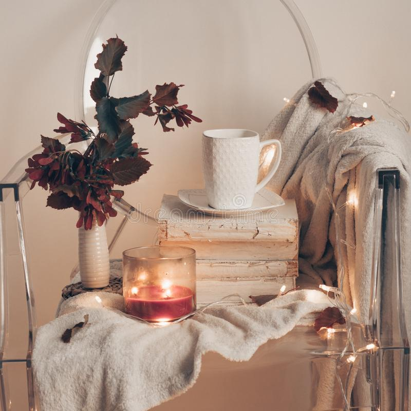 Na plastikowym przejrzystym krześle Ciepły bedspread, filiżanka herbata na książkach i świeczka z jesień liśćmi -, jesieni zimy p obrazy stock