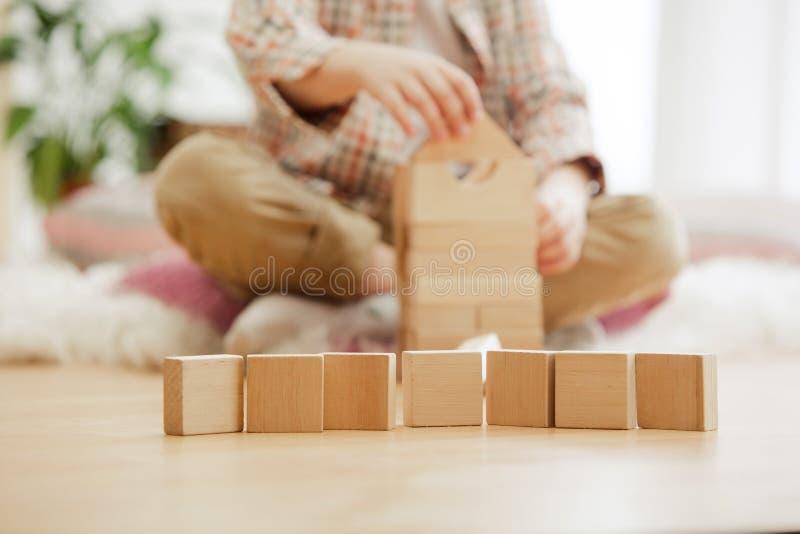Na podłoga małego dziecka obsiadanie Ładna chłopiec palying z drewnianymi sześcianami w domu zdjęcie stock
