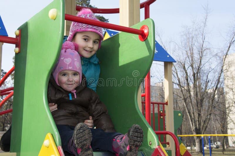 Na primavera de duas meninas que jogam no campo de jogos fotografia de stock