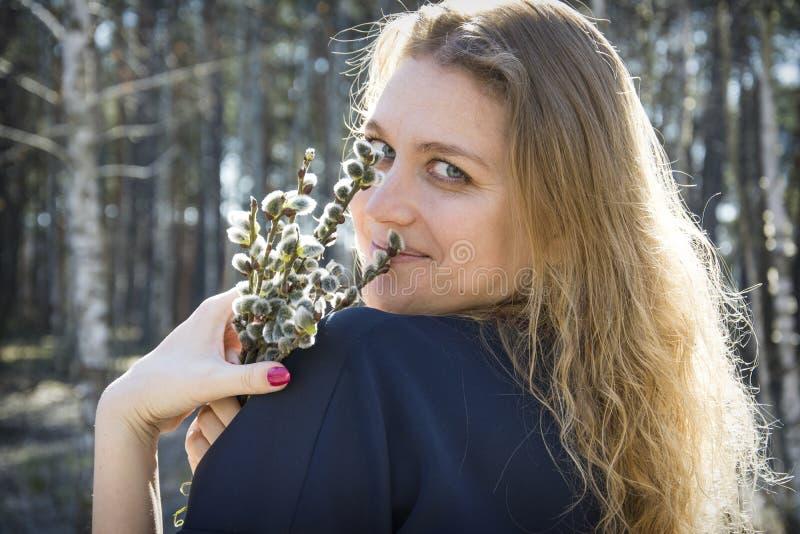 Na primavera na menina da floresta com um ramalhete do salgueiro Aprecia o perfume imagem de stock royalty free