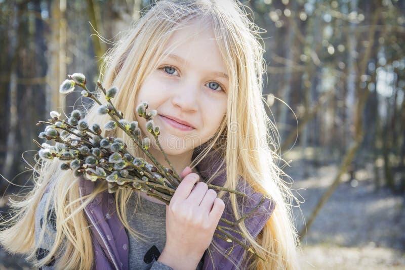 Na primavera na menina da floresta com um ramalhete do salgueiro Aprecia o perfume imagens de stock royalty free