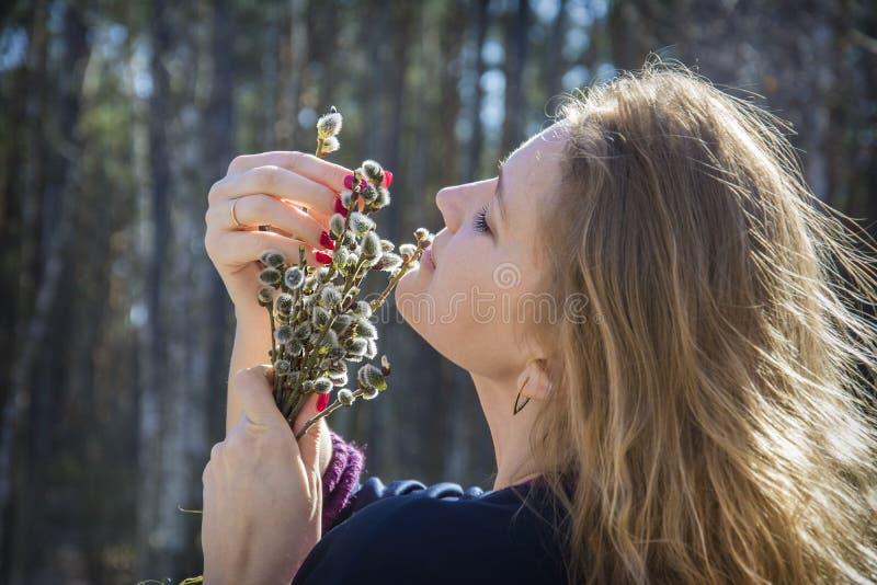 Na primavera na menina da floresta com um ramalhete do salgueiro Aprecia o perfume imagens de stock